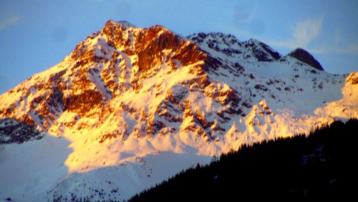 Die letzten Sonnenstrahlen tauchen den Gipfel in flammendes Rot